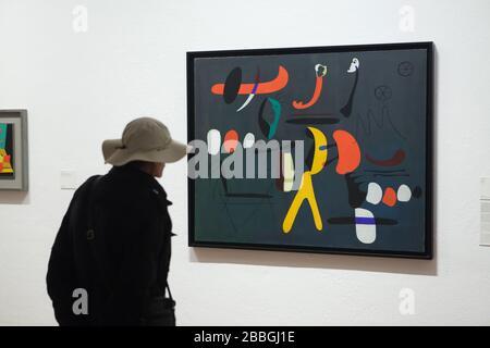 """Visiteur devant la peinture du peintre moderniste espagnol Joan Miró intitulée """"Peinture"""" (1933) affichée dans la Fundació Joan Miró (Fondation Joan Miró) à Barcelone, Catalogne, Espagne. Banque D'Images"""