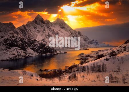 arbres de lumière du soleil qui brille à travers les nuages au-dessus des montagnes enneigées autour du fjord.