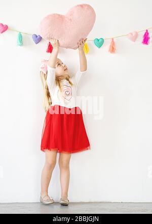 jolie jeune fille tenant un oreiller rose coeur sur la tête Banque D'Images