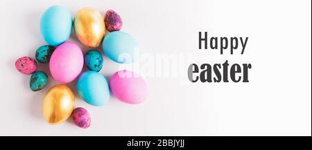 Joyeuses Pâques concept. De grands petits œufs de différentes couleurs tendance se trouvent dans une pile sur un fond blanc texte joyeuses Pâques. Cadre horizontal isolé. F Banque D'Images