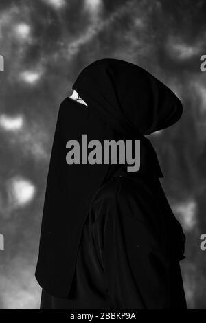 Profil d'une femme musulmane regardant vers le haut. Image en noir et blanc.
