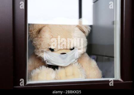 L'ours en peluche dans un masque médical de visage regarde hors de la fenêtre. Concept de quarantaine du coronavirus pendant l'épidémie COVID-19