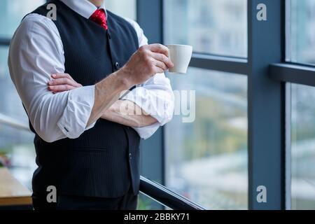 Sourire heureux directeur général pense à son développement de carrière réussi tout en se tenant avec une tasse de café dans sa main dans son bureau près de la