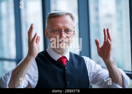 Sourire heureux directeur général pense à son développement de carrière réussi alors que se tient dans son bureau près de l'arrière-plan d'une fenêtre avec copie sp