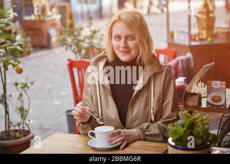 Une jeune femme caucasienne souriante se détend dans un café de rue à Istanbul avec une tasse de café. Blanc femmes voyages touristiques en Turquie.
