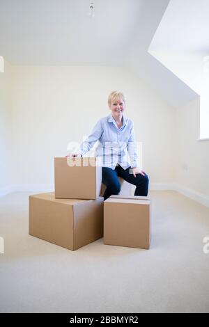 Portrait de la femme âgée réduction de la taille en retraite assis sur des boîtes à la Nouvelle maison le jour de déménagement Banque D'Images