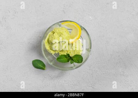 Dessert végétalien maison, crème glacée avocat avec feuilles de citron et de menthe dans un bol en verre sur fond gris. Vue de dessus avec espace de copie Banque D'Images