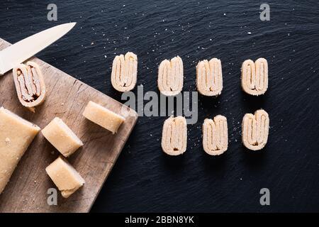 Concept alimentaire pâte feuilletée bio maison pour les palmiers français, les pâtisseries chinoises aux papillons ou les oreilles d'éléphant sur tableau noir en ardoise