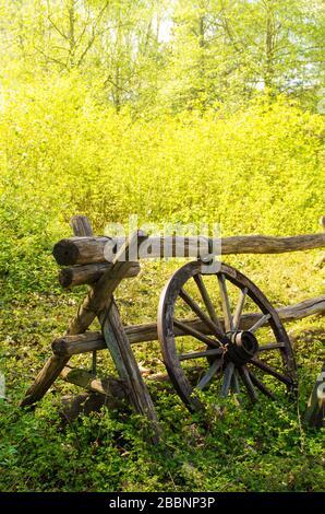 Ancienne roue de wagon à côté d'une clôture en bois dans la campagne. Banque D'Images