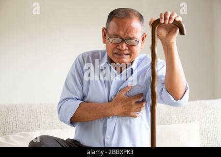 Un vieil homme asiatique assis sur un canapé et avoir une douleur au coeur, crise cardiaque à la maison. Concept de soins de santé. Banque D'Images