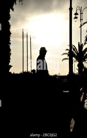 Silhouette d'un homme dans un manteau et un chapeau sur la côte de la mer au coucher du soleil. Concept de mystère ou de solitude. Convient pour une couverture d'un livre de thriller. Espace de copie pour le sommet Banque D'Images