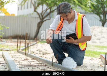 L'ingénierie, portant un casque et holding tablets, s'assoir pour vérifier la structure du couloir dans le parc