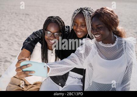 Portrait de joyeux amies adolescentes prenant un selfie à la plage Banque D'Images