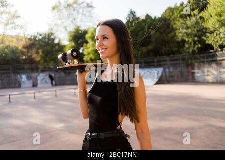 Jeune femme avec planche à roulettes sur son épaule dans un parc de skateboard