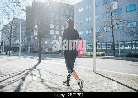 Jeune femme sportive avec prothèse de jambe marchant dans la ville