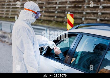 Homme portant des vêtements de protection contrôlant l'homme principal en voiture Banque D'Images