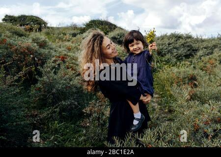 Bonne mère et petite fille avec fleurs cueillies dans la nature, la Haye, Pays-Bas