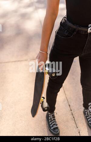 Jeune femme tenant son skateboard dans un parc de skateboard