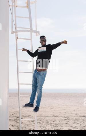 Un jeune homme élégant debout sur une échelle à la plage
