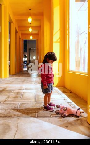Une fille triste regardant le jouet unicorn couché sur le sol Banque D'Images