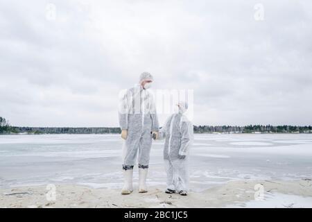 Père et fils portant des vêtements de protection debout sur une rivière gelée Banque D'Images