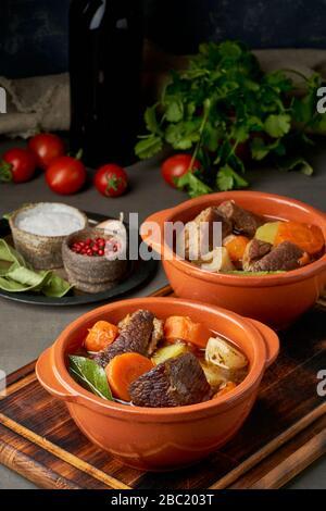 Goulash avec de grands morceaux de boeuf et de légumes. Viande de Bourgogne. Cuisson lente dans deux casseroles ou une poêle en fonte. Fond sombre. Vertical Banque D'Images