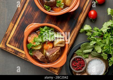 Goulash avec de grands morceaux de boeuf et de légumes. Viande de Bourgogne. Cuisson lente dans deux casseroles ou une poêle en fonte. Fond sombre. Vue de dessus, bannière Banque D'Images