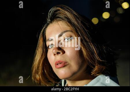 Gros plan portrait du visage d'une belle jeune femme aux cheveux sombres au crépuscule Banque D'Images