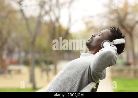 Vue latérale portrait d'un homme noir portant un casque sans fil reposant assis sur un banc dans un parc écoutant de la musique Banque D'Images