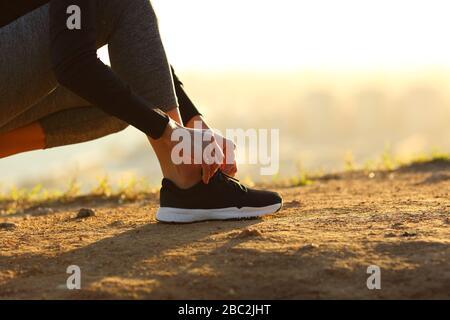 Vue latérale près de la femme de coureur mains nouant des lacets de chaussures sur le sol au coucher du soleil