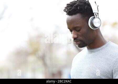 Homme noir pensif portant un casque à l'écoute de la musique regardant vers l'extérieur debout Banque D'Images