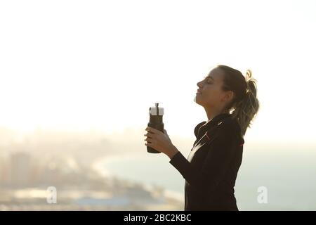 Profil d'une femme de coureur qui se détend respirer de l'air frais tenant une bouteille d'eau avec la ville en arrière-plan
