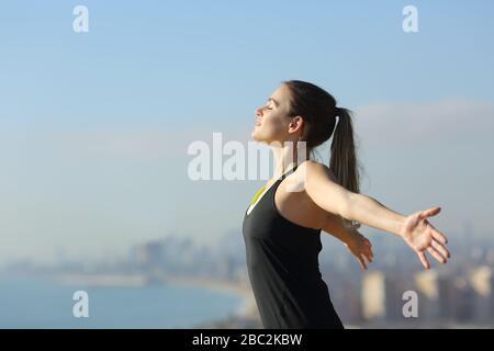 Vue latérale portrait d'un coureur détendu respirent l'air frais dans la périphérie de la ville une journée ensoleillée