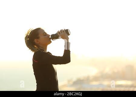 Vue latérale portrait d'une femme de coureur buvant de l'eau à partir d'une bouteille hydratante après l'exercice dans une périphérie de la ville