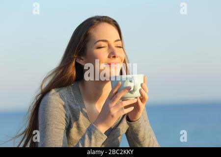 Femme satisfaite des yeux fermés qui boivent du café au coucher du soleil sur la plage