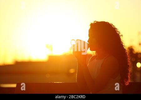 Silhouette d'une femme qui boit du café assis sur un banc au coucher du soleil