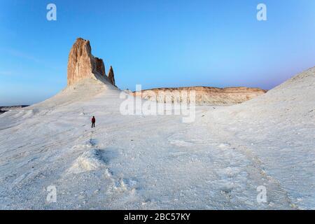 Femme regardant sous des formations rocheuses et en regardant la vue panoramique, plateau d'Ustyurt, Bosjira, la dépression Caspienne, Aktau, Mangystau, Kazakhstan Banque D'Images