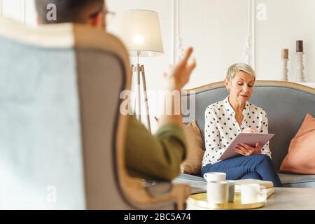Une psychothérapeute professionnelle écrit ses idées Banque D'Images