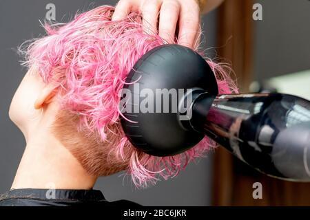 Les mains du coiffeur sèche les cheveux roses de la femme gros plan.