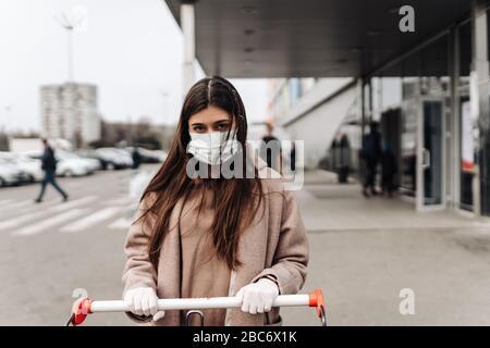 Jeune femme portant un masque de protection contre le coronavirus 2019-nCoV poussant un panier.
