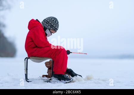 Un garçon en salopette rouge sur la pêche d'hiver sur le lac. Siège dans un fauteuil près du trou. Entre les mains d'une canne à pêche. Regarde attentivement la tringle de pêche. L'horizon fusionne avec le ciel. Banque D'Images