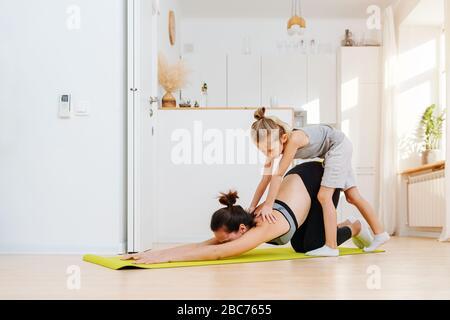 Mère faisant du yoga s'étirant sur le tapis, son petit fils appliquant la pression Banque D'Images