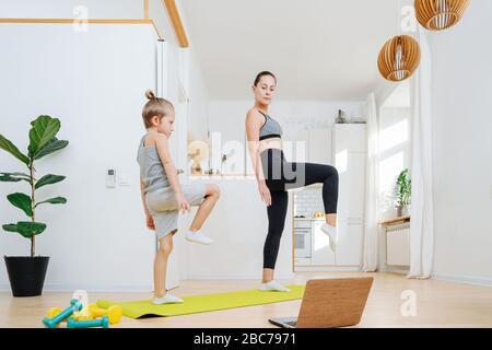 Maman et son faisant du yoga, debout sur une jambe, regardant l'ordinateur portable Banque D'Images