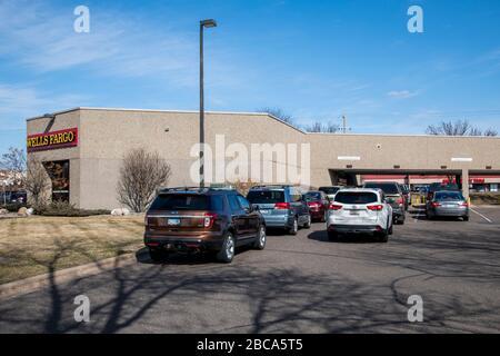 Maplewood, Minnesota. Avec le hall d'entrée fermé la circulation se sauvegarde à la fenêtre de lecteur à la banque de Wells Fargo car les gens prennent de l'argent à cause de th Banque D'Images