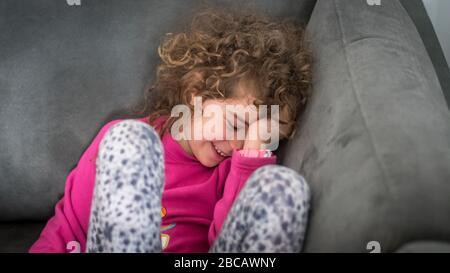 Portrait isolé et étroit d'une jeune fille de 7 ans assise dans le canapé de la pièce de départ et souriant Banque D'Images