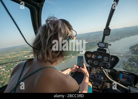 Les femmes blondes magnifiques qui prennent leur vol et prennent leur selfie avec un smartphone en hélicoptère. Elle porte des écouteurs pilotes. Banque D'Images
