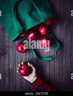 Livraison d'achats en ligne. Sac écologique avec pommes rouges. Femme tenant la pomme sur fond en bois sombre