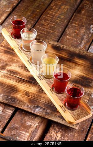 Ensemble coloré de cocktails alcoolisés dans des tireurs de verres sur une table en bois pour une fête alcoolique. Ensemble de vin, brandy, liqueur, teinture, cognac, W