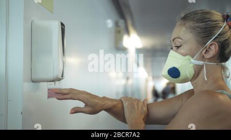 Fermez les mains de lavage à l'aide d'un distributeur automatique de solution désinfectante antibactérienne à l'alcool à l'aéroport. Femme portant un masque respiratoire médical. Banque D'Images