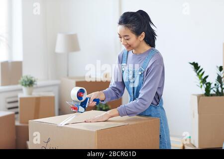 Portrait d'une femme asiatique souriante qui emballe des boîtes en carton avec un distributeur de ruban tout en se déplaçant vers la nouvelle maison, espace de copie